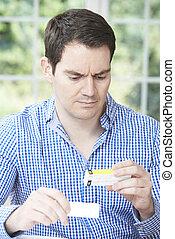 Man Reading Information On Drug Packaging