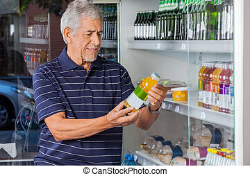 Man Reading Information On Juice Bottle