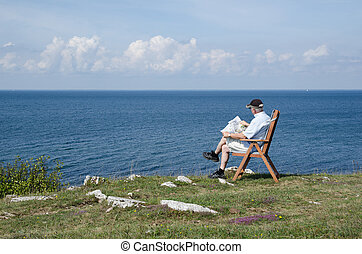Man reading newspaper at seaside with beautiful view