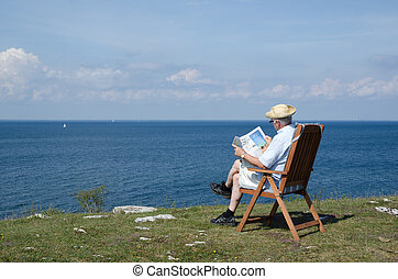 Man reading newspaper in a chair at a beautiful view