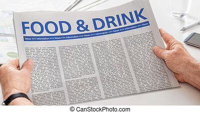 Man reading newspaper with the headline Food and Drink