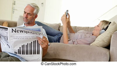 Man reading paper while partner is listening to music