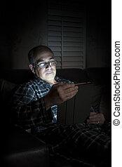 Man reading tablet at night