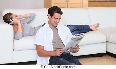 Man reading the newspaper while his girlfriend is listening music
