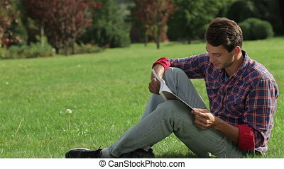 Man reading while sitting on the grass