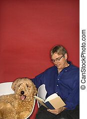 Man reading with goldendoodle dog.