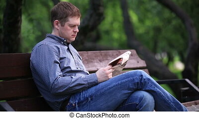 Man reads newspaper on bench in the park 2