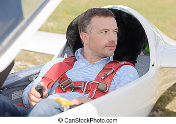 man ready to fly inside the cockpit of a glider