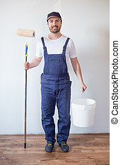 Man ready to paint one wall holding painting tools