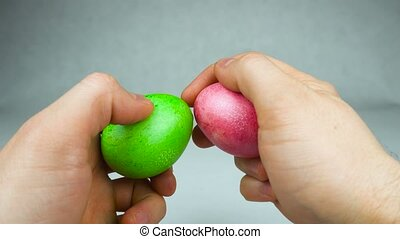 Close up of hands before the traditional Easter game Egg jarping during Christian feast Pascha or Resurrection Sunday played by hard boiled Decorated eggs