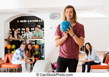 Man Ready With Bowling Ball in Club