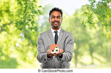 man realtor with house model and folder - real estate ...