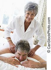 Man receiving a massage from a woman