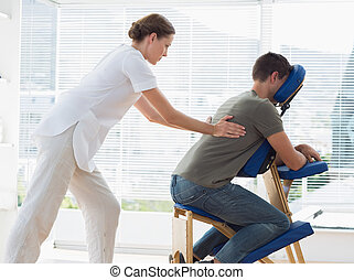 Man receiving back massage from phy - Side view of man...