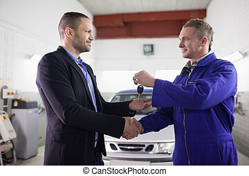 Man receiving car key while shaking hand to a mechanic in a...
