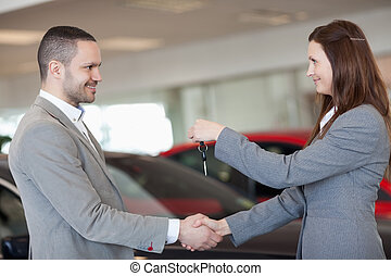 Man receiving car keys while shaking hand