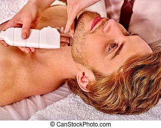 Man receiving electric facial peeling massage. - Man...