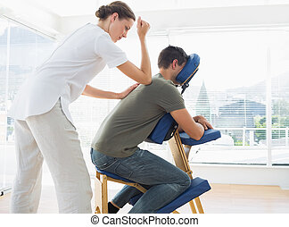 Man receiving massage from physioth - Side view of man...