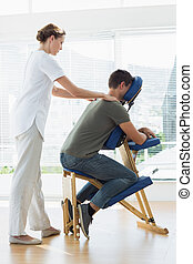 Man receiving shoulder massage from - Full length of man...