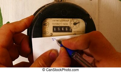 A man records the readings of an old electricity meter with cyrillic characters on the case