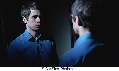 Young man looking in the mirror