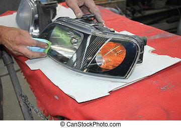 Man refurbishing car headlight - Man refurbishing a car...