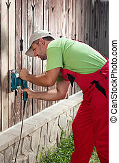 Man refurbishing old wooden fence - removing cracked paint...