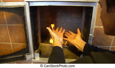 Man relax by warm fire and warming up his hands, nice comfortable fireplace in a house outside the city