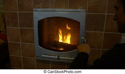 Man relax by warm fire and warming up his hands, open and zoom in, nice comfortable fireplace in a house outside the city
