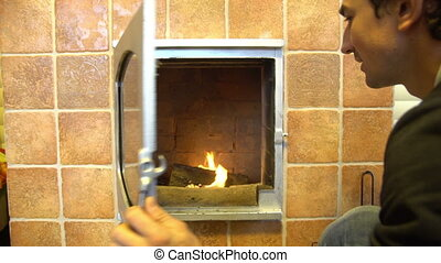 Man relax by warm fire and warming up his hands, open nice comfortable fireplace in a house outside the city
