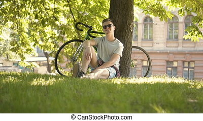 Man Relaxes under Tree - Smiling young man in black...
