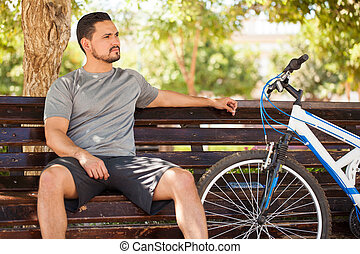 Man relaxing after a long bike ride at the park