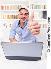 man relaxing at home with laptop computer showing thumbs up