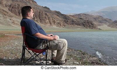 Man relaxing at mountain lake