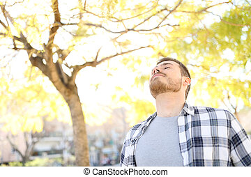 Man relaxing breathing deep fresh air in a park