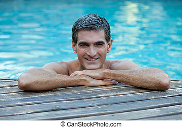 Man Relaxing by Pool's Edge - Portrait of smiling man...