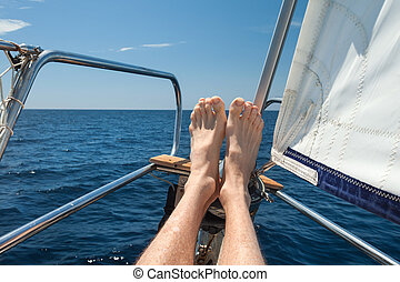 Man relaxing his feet on a sailboat.