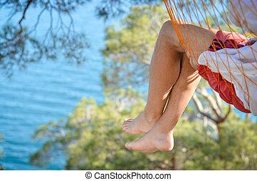 Man relaxing in a hammock on a beautiful sand beach. Cozumel, Mexico, Caribbean Sea.