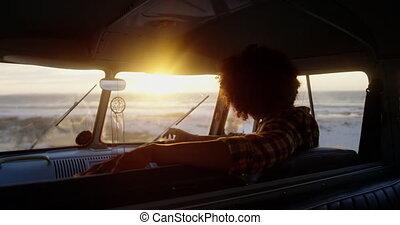 Man relaxing in camper van at beach 4k