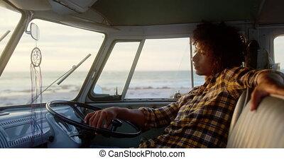 Man relaxing in camper van at beach 4k - Side view of ...