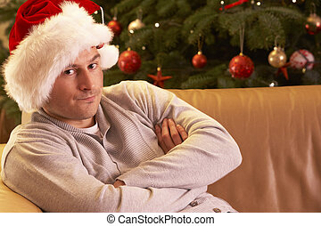 Man Relaxing In Front Of Christmas Tree