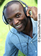 Man relaxing in garden with headphones on