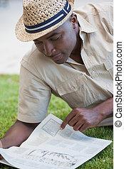 Man relaxing in his garden reading