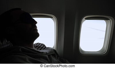 Man relaxing in sleeping mask in the airplane. Professional shot in 4K resolution. 040. You can use it e.g. in your commercial video, medical, business, presentation, broadcast