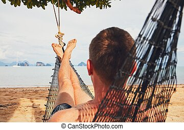 Man relaxing in the hammock - Young man (tourist) relaxing...