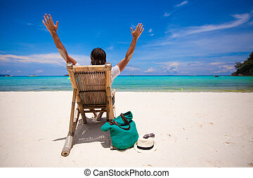 Man relaxing in the wooden chair on sand beach