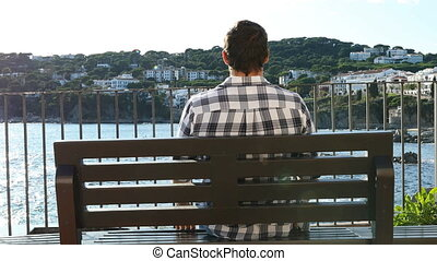 Man relaxing sitting on a bench contemplating views on the beach in a coast town