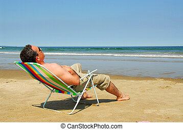 Man relaxing on beach - Man relaxing in a beach chair on the...