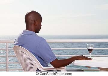 man relaxing on sea view balcony