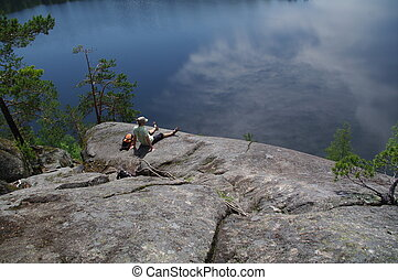 man relaxing on the top of a cliff